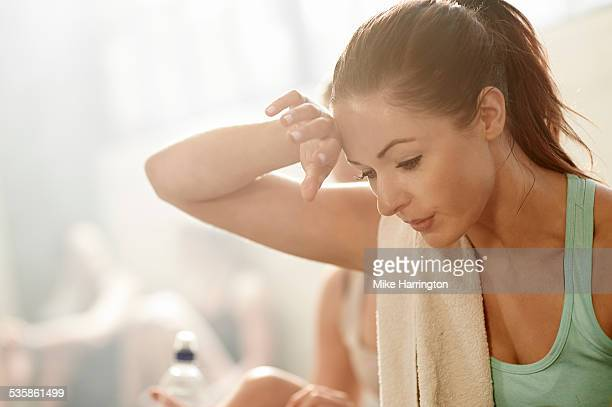 healthy young female wiping sweat from her brow - effort stock pictures, royalty-free photos & images