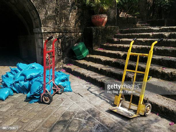 Heap Of Blue Sacks With Push Carts On Street By Steps