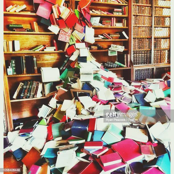 heap of books on floor in library - abundance stock pictures, royalty-free photos & images
