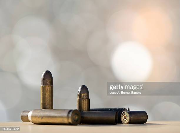 Heap of bullets and tips of firearms illuminated by the light of the Sun