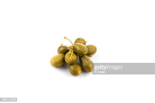 Heap of canned capers on a white background
