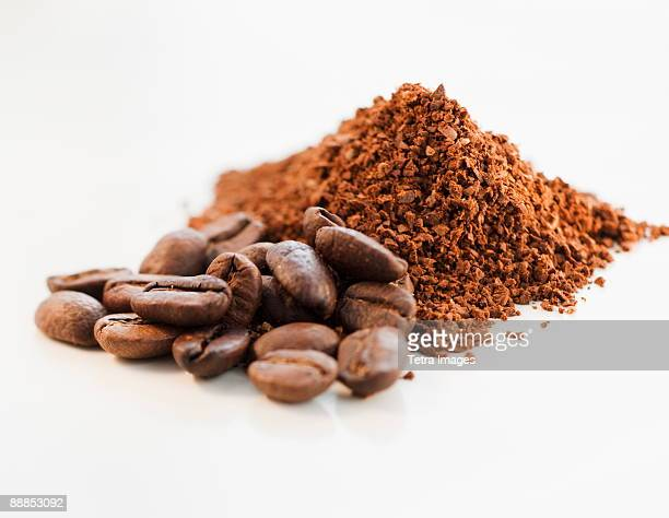 heap of coffee beans and ground coffee - café moulu photos et images de collection
