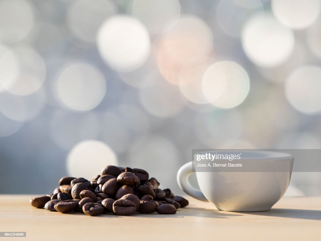 Heap of coffee beans toasted and a cup of coffee  on a table of wood illuminated by the light of the Sun : Stock Photo