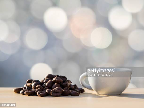 heap of coffee beans toasted and a cup of coffee  on a table of wood illuminated by the light of the sun - taza de café stock pictures, royalty-free photos & images