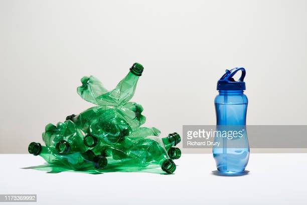 a heap of disposable water bottles next to a reusable water bottle - plastic stockfoto's en -beelden