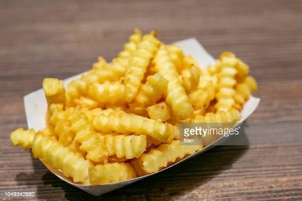 heap of french fries in a box - fast food french fries stock pictures, royalty-free photos & images