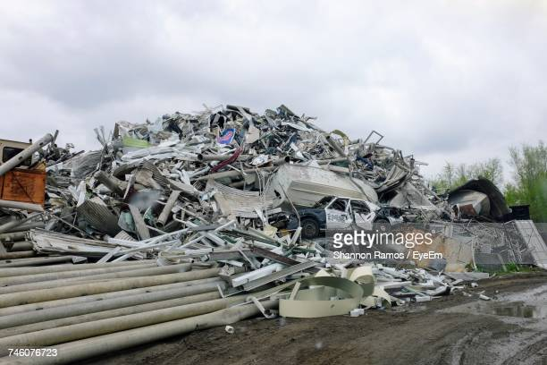 heap of garbage at junkyard against cloudy sky - junkyard stock photos and pictures