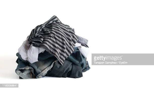 heap of laundry against white background - heap stock pictures, royalty-free photos & images