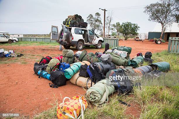 Heap of luggage on field by car against clear sky