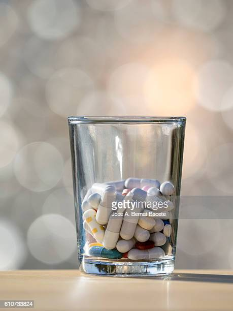 Heap of medicines in tablets and pills of colors, inside a glass glass