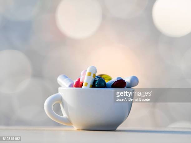 Heap of medicines in tablets and pills of colors, inside in a cup of coffee
