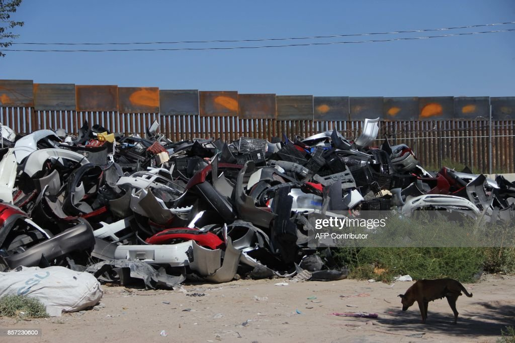 A heap of old car parts in a section of the metal barrier between ...