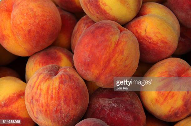 a heap of ripe peaches (prunus persica) close-up - peach stock photos and pictures