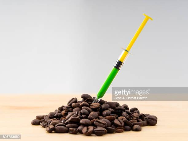 Heap of roasted coffee with a laboratory syringe nailed to an experiment ; food concept transgenic and modified genetically.