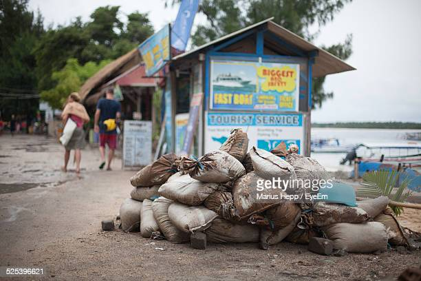 heap of sacks on sand against market stall on beach - sandbag stock pictures, royalty-free photos & images