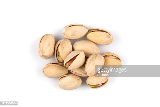 heap of salted pistachio nuts isolated on white background - cashew stock pictures, royalty-free photos & images