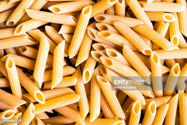 heap of uncooked whole wheat penne italian pasta, top view. pasta pattern. food background. - pasta stock pictures, royalty-free photos & images