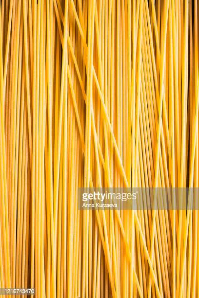 heap of uncooked whole wheat spaghetti italian pasta, top view. pasta pattern. food background. - spaghetti stock pictures, royalty-free photos & images
