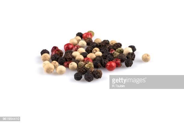 heap of various pepper peppercorns seeds mix on white - pfeffer stock-fotos und bilder
