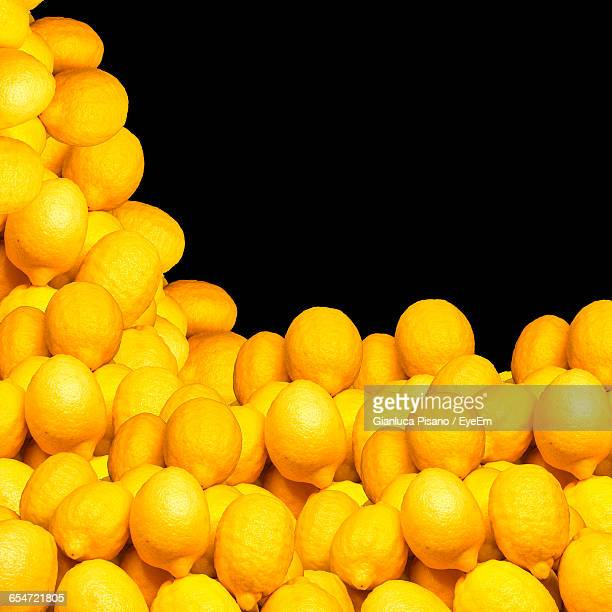 Heap Of Yellow Lemons Against Black Background