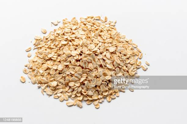 heaps of oat flake on white background - raw food stock pictures, royalty-free photos & images