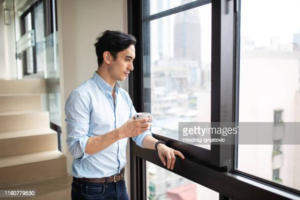 hearing impaired man drinking morning coffee near window - taiwan stock pictures, royalty-free photos & images
