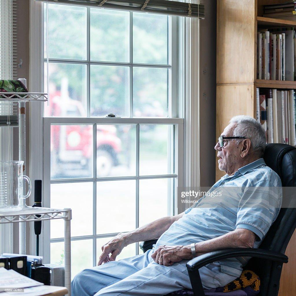 Hearing Impaired Senior Adult Man Looking Through Window : Stock Photo