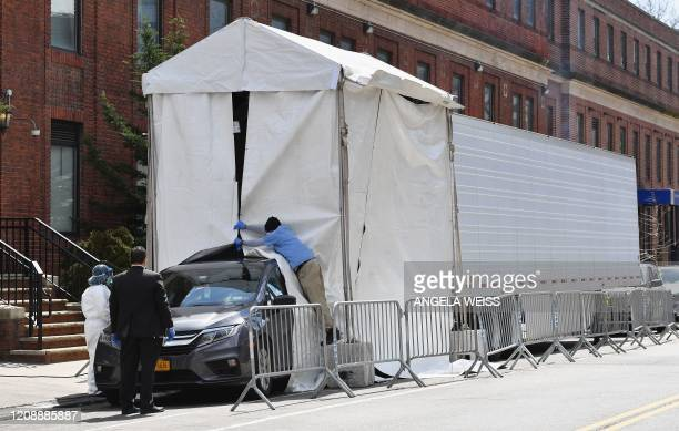 Hearse car backs into a refrigerated truck to pick up deceased bodies outside of the Brooklyn Hospital on April 1, 2020 in New York City.