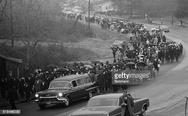 Hearse carrying the body of Jimmie Lee Jackson drives slowly in rain with an estimated 700 people, mostly African American, following the cemetery...