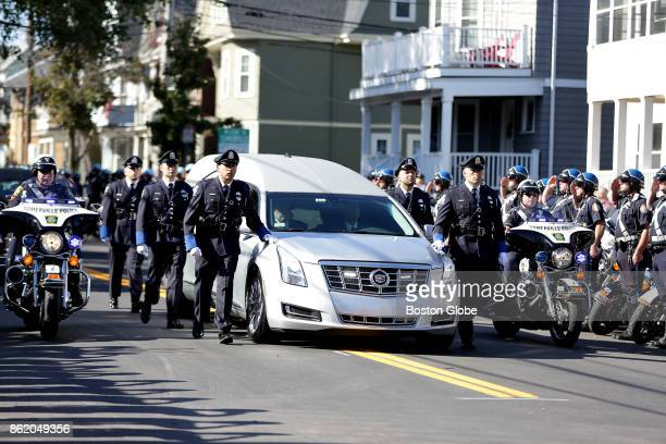 A hearse carrying the body of Somerville police officer Louis M Remigio is escorted by his fellow officers to St Clement Church in Medford MA for his...