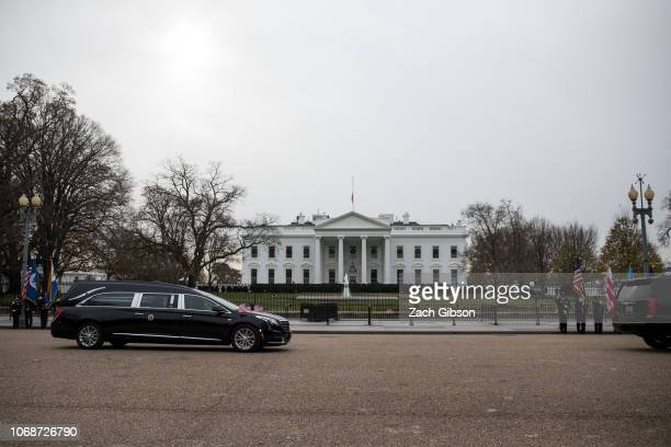 A hearse carrying the remains of former US President George HW Bush drives past the White House en route to the National Cathedral before a state...