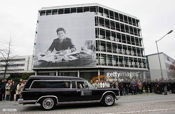 A hearse containing the body of Aenne Burda passes a picture of her hanging on the Burda publishing house after the funeral service on November 10...
