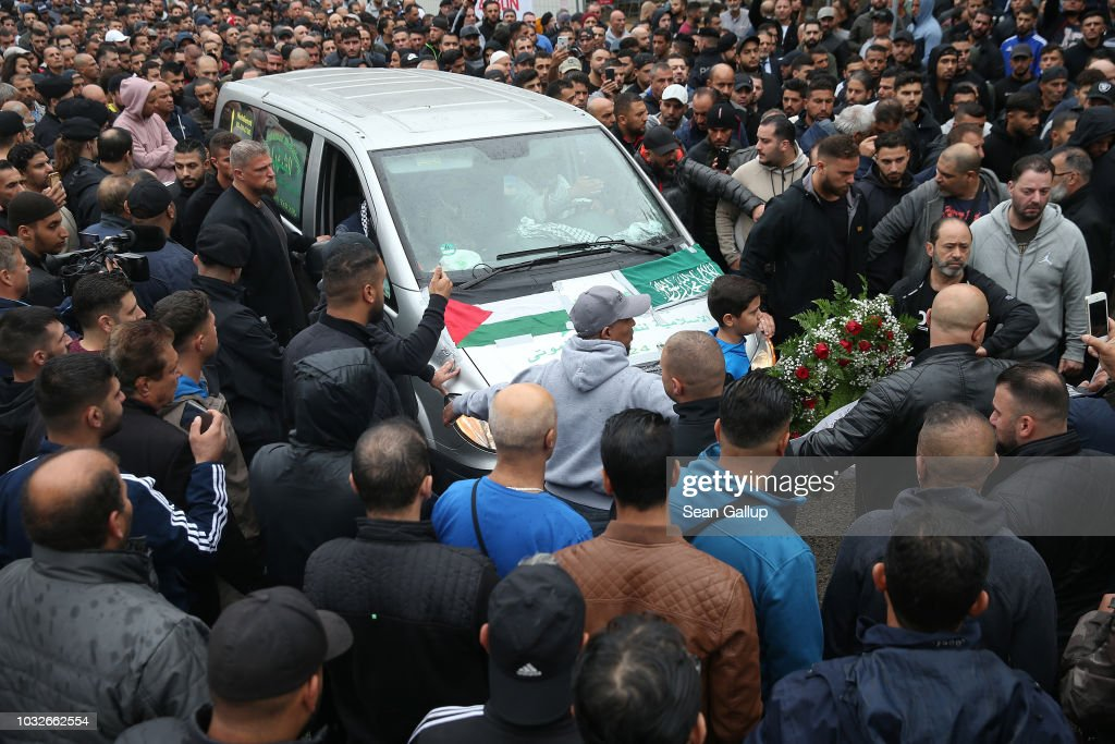 A hearse draped with a Palstinian flag arrives carrying the body of Nidal R., an associate of a Berlin Arab clan, through a crowd gathered at the New 12 Apostles cemetery on September 13, 2018 in Berlin, Germany. Nidal R., 36, a multiple felon, was gunned down by assailants who managed to flee the scene at a public park last Sunday. Berlin has a growing number of Arab, Kurdish and Turkish clans involved in organized crime.