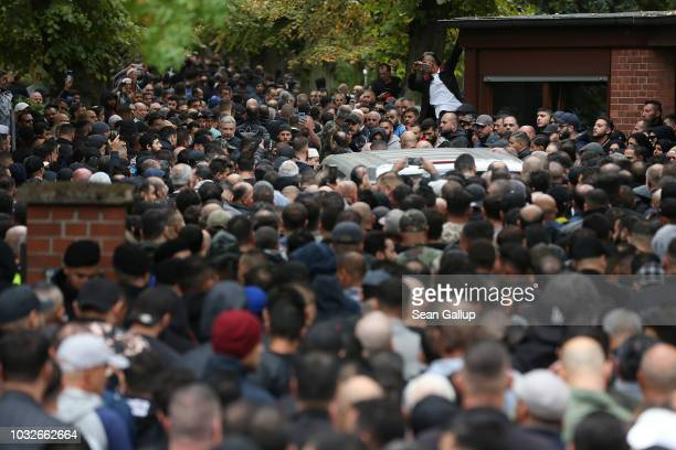 A hearse draped with a Palstinian flag arrives carrying the body of Nidal R an associate of a Berlin Arab clan through a crowd of mourners gathered...