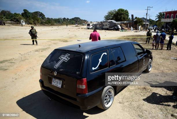 A hearse waits near the site of the accident where a military helicopter fell on a van in Santiago Jamiltepec Oaxaca state Mexico on February 17 2018...