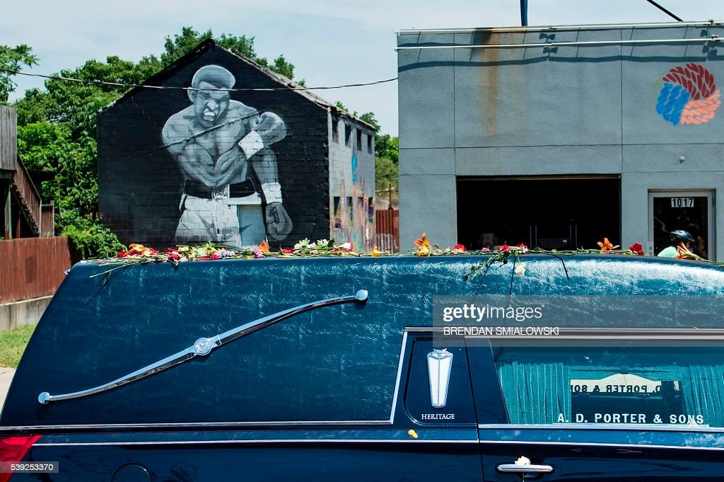 TOPSHOT - A hearse with the remains of boxing legend Muhammad Ali passes a mural depicting his 1965 victory over Sonny Liston on the way to Cave Hill Cemetery June 10, 2016 in Louisville, Kentucky. Thousands of people from near and far were expected to line the streets of Muhammad Ali's hometown Louisville on Friday to say goodbye to the boxing legend and civil rights hero, who mesmerized the world with his dazzling skills. / AFP PHOTO / Brendan Smialowski