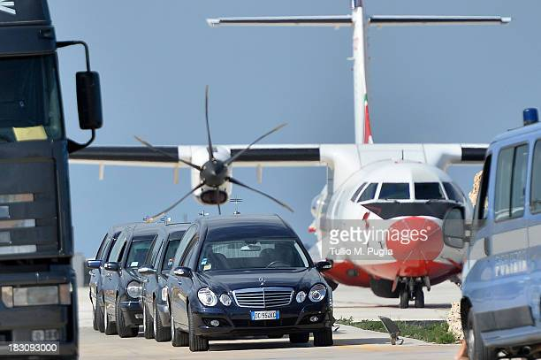 Hearses arrive at the Lampedusa airport where bodies of migrants lie on October 4 2013 in Lampedusa Italy The search for bodies continues off the...