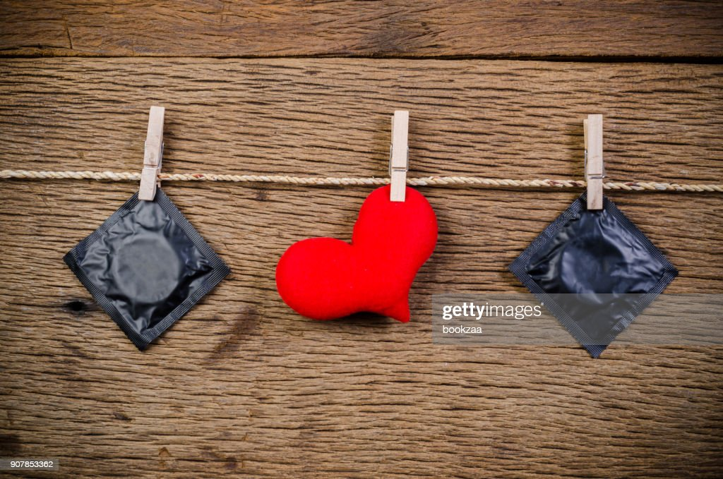 heart and condoms hanging on clothesline : Stock Photo