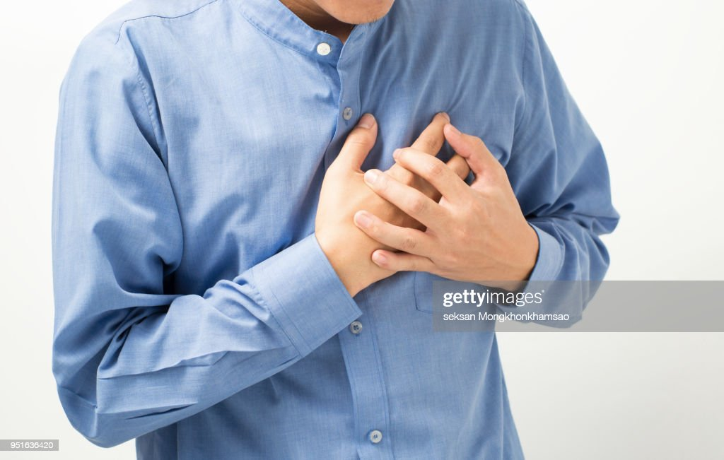 Heart attack concept. Young man suffering from chest pain, close up : Stock Photo