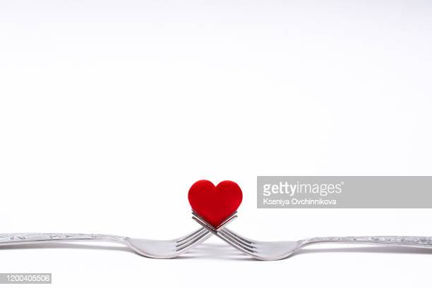 heart between two forks on a table set for two, close up - valentines day dinner stock pictures, royalty-free photos & images