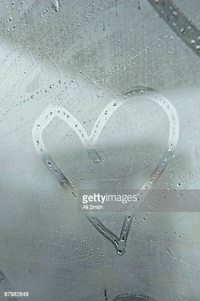 heart drawn on fogged window - mirror steam stock photos and pictures
