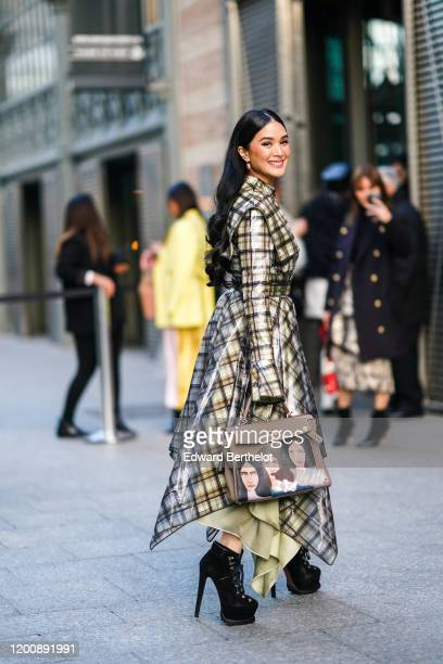Heart Evangelista wears earrings, a light yellow dress under a transparent vinyl checkered dress with a handkerchief hem, a taupe-color handbag with...