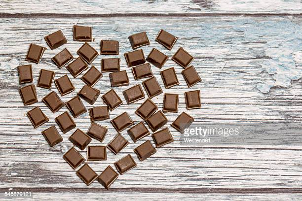 Heart formed by pieces of chocolate on wood
