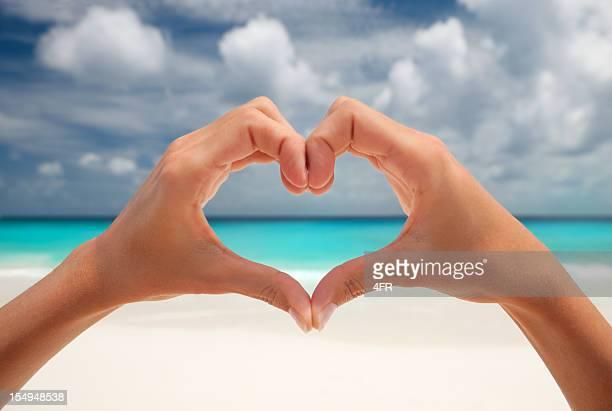 Herz-Geste mit der Hand am Strand
