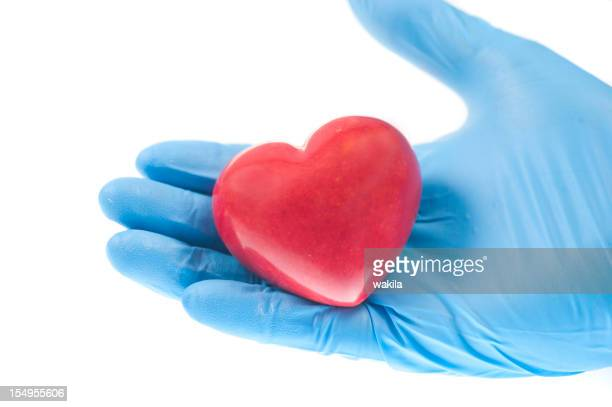 heart in hand with blue medical gloves