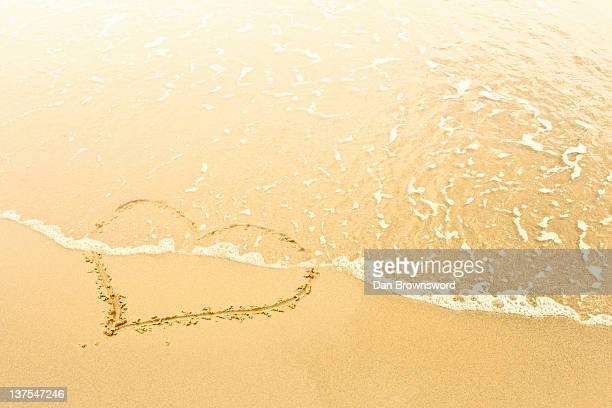 Heart in sand washed away by waves