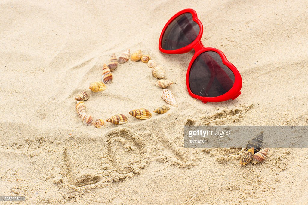 Heart of shells and sunglasses on sand at the beach : Stock Photo