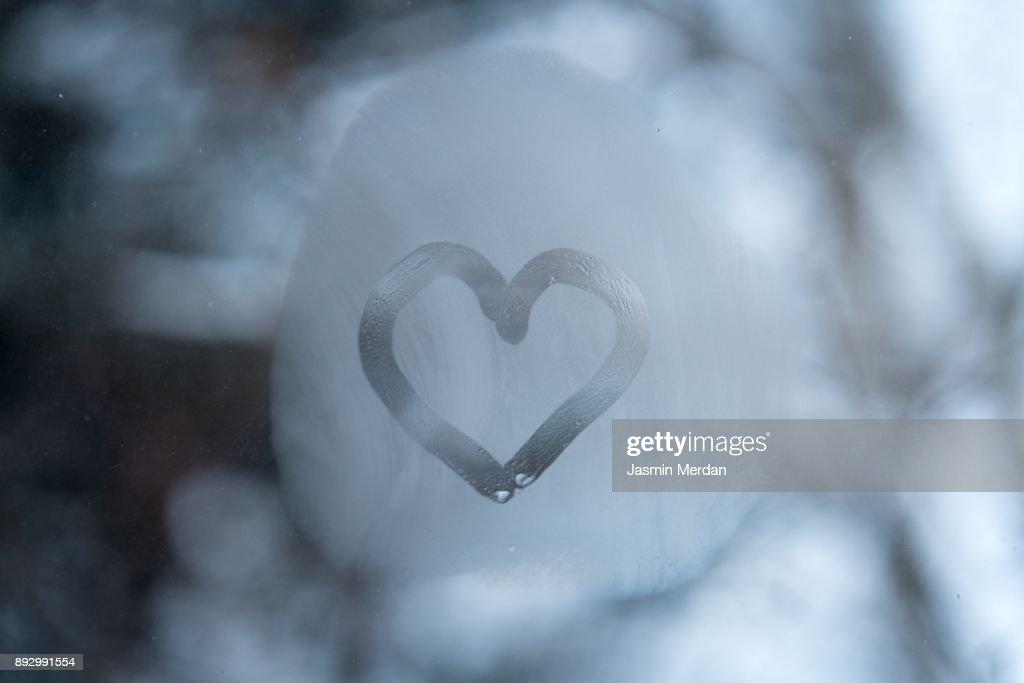 Heart on frozen window : Stock Photo
