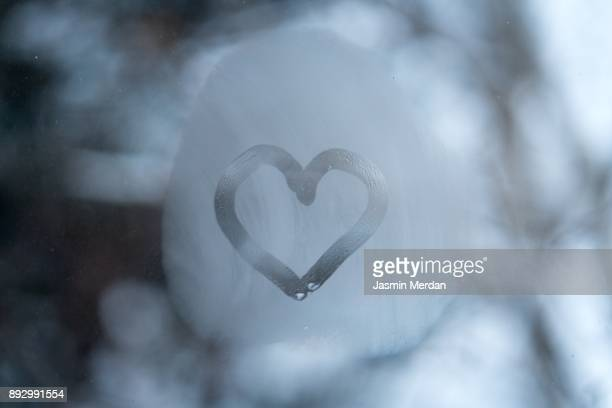 heart on frozen window - heart month stock photos and pictures