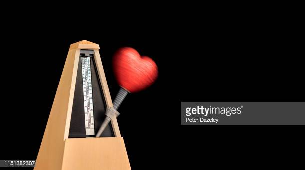 heart on moving metronome - beating heart stock pictures, royalty-free photos & images